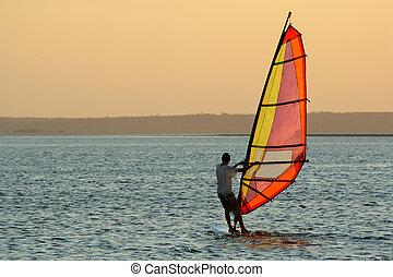 Windsurfer - Backlit windsurfer at sunset on calm coastal...