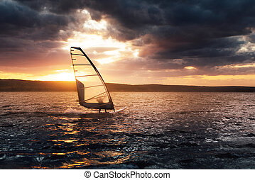 Windsurfing on a lake at sunset.