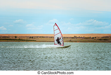 Windsurfing Sport sailing water active leisure Windsurfer on lake summer day