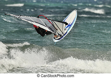 Young windsurfer jumping high over the wave.