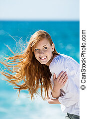 Windswept beautiful woman at the sea