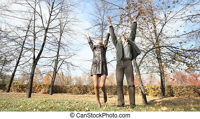 Windy autumn - Young people throwing fallen leaves together...