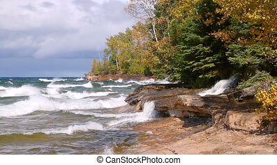 Looping video features Elliot Falls waterfall pouring into a turbulent Lake Superior on a windy day at Miners Beach in Pictured Rocks National Lakeshore, near Munising on the Upper Peninsula of Michigan.