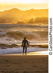 Windy day on the spanish coastal in Palamos with a surfer on the beach
