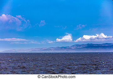 Windy day, waves on the sea and blue sky with white clouds. Greek island background.
