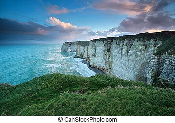 windy sunrise over cliff in Atlantic ocean, Etretat, Normandy, France