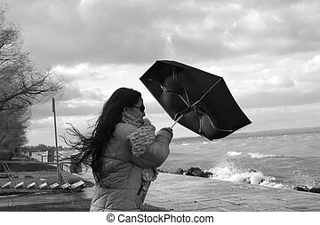 Windy weather - Digital photo of a woman with an umbrella at...
