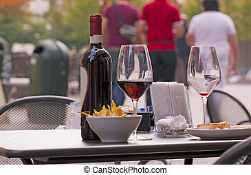 Glasses of wine and appetizers on a table, outdoors