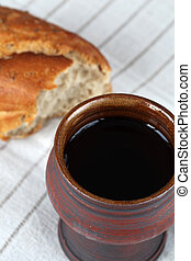 Chalice with red wine and bread in background. Shallow dof