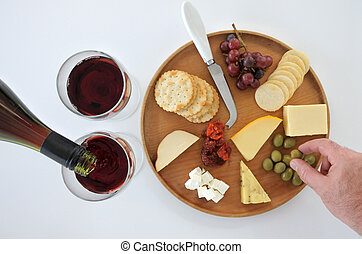 Wine and cheese platter - Red wine poured into two ...
