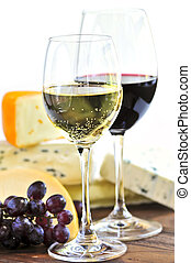 Wineglasses with red and white wine and assorted cheeses