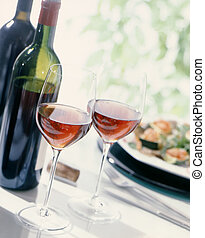 Two wine glasses, along with bottles of wine and a plate with food,