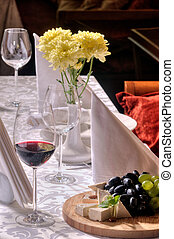 Wine and grapes and cheese on the table