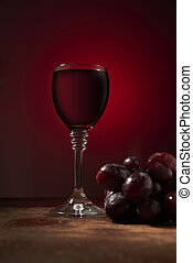 wine and grapes on a red background