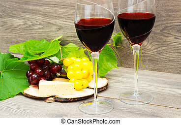 wine and grapes on a wooden background