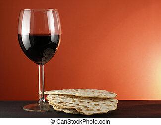 Wine and matzoh - Glass of wine and matzoh over red...