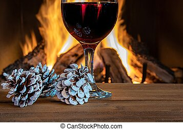 wine and pine cones by fireplace