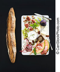 Wine and snack set. Baguette, figs, grapes, nuts, cheese variety, meat appetizers, herbs on white wooden board over black grunge background, top view.