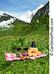 Wine and vegetables served at a picnic on Alpine meadow. Switzerland