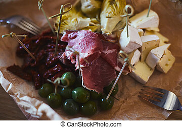 Wine appetizer set with jamon, olives, cheese, dried tomatoes and artichoke, beautifully decorated catering banquet with different food snacks and appetizers, tapas starters on party event