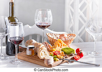 Wine, baguette and cheese on wooden background - The red...