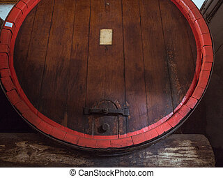 Wine barrel stacked in the old cellar of the winery close up.