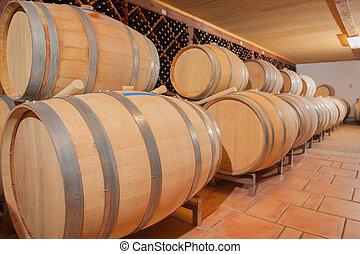 Wine Barrels and Bottles Age Inside Cellar - Wine Barrels...