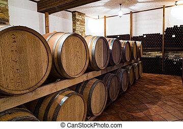 Wine barrels in Greece - Stacked wine barrels and bottles in...