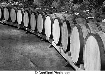 Wine barrels stacked in the old cellar of the winery, black...