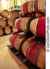 Wine barrels - Stacked oak wine barrels in winery cellar