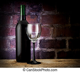Wine bottle and glass on brick back