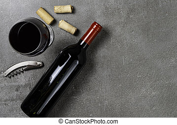 Wine bottle, cup, corks and opener on concrete background. Copy Space