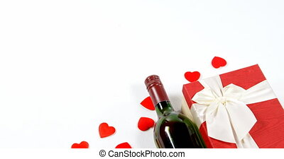 Wine bottle, gift box and scattered red hearts on white surface 4k
