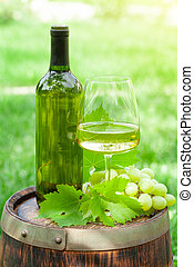 Wine bottle, glass and grape on old wine barrel