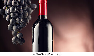 Wine. Bottle of red wine with ripe grapes over black background