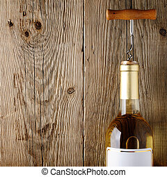 Wine bottle with corkscrew on wooden background