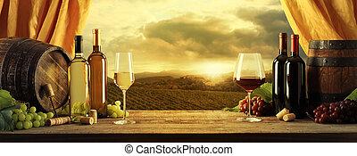 Wine bottles, barrels and vineyard in sunset