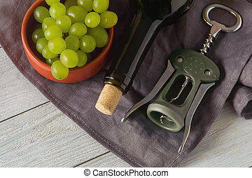 wine bottles, glass, corkscrew, grapes on table. top view.