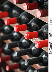 wine bottles in cellar - wine bottles with red caps in racks...
