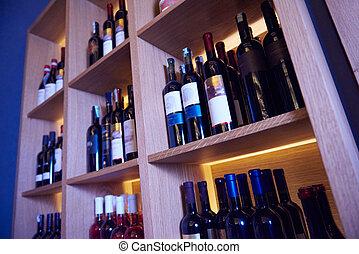 Wine bottles on a wooden shelf.
