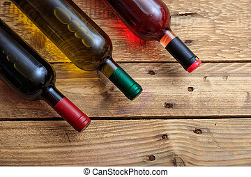 Wine bottles on wooden background, top view, copy space