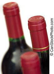 Three unopened wine bottles, isolated on white. Focus on middle bottle/cap.