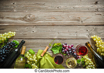 Wine bottles with grapes and corks on wooden background with...