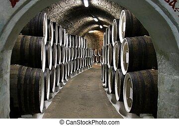 Wine cellar - Wine barrels in cellar with casks along the...