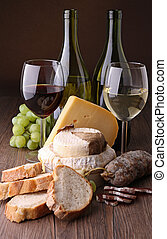 wineglass with cheese, sausage and grapes