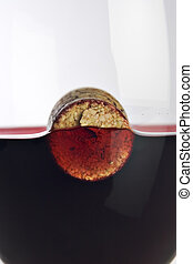 wine cork floating in a glass of wi