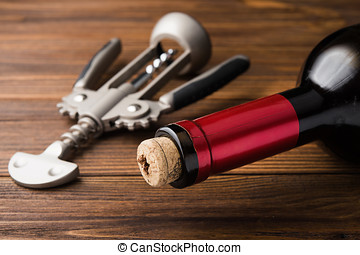 wine corkscrew and bottle on wooden table