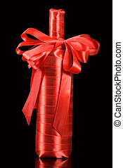 A wine bottle wrapped in red ribbon with a bow - isolated in black