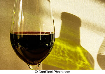 the shadow of a glass and a bottle of wine
