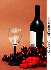 Wine glass, grapes and bottle on biege background